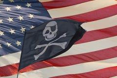 Wellenartig bewegende Piratenflagge lustiger Roger auf USA-Sternenbanner - Lizenzfreies Stockbild