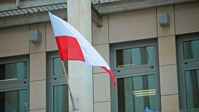 Wellenartig bewegende polnische Flagge auf Gebäudeabschluß oben stock footage