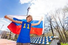 Wellenartig bewegende russische Flagge des sportlichen Teenagers am Stadion Lizenzfreies Stockfoto