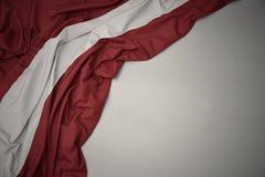 Wellenartig bewegende Staatsflagge von Lettland auf einem grauen Hintergrund stockfoto