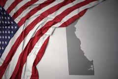 Wellenartig bewegende Staatsflagge von Staaten von Amerika auf einem grauen Delaware geben Kartenhintergrund an Stockfotografie