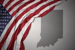 Wellenartig bewegende Staatsflagge von Staaten von Amerika auf einem grauen Indiana geben Kartenhintergrund an stockfotos