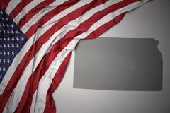 Wellenartig bewegende Staatsflagge von Staaten von Amerika auf einem grauen Kansas geben Kartenhintergrund an lizenzfreie stockfotos