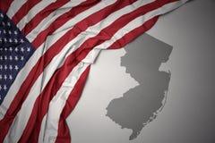 Wellenartig bewegende Staatsflagge von Staaten von Amerika auf einem grauen New-Jersey geben Kartenhintergrund an stockbilder