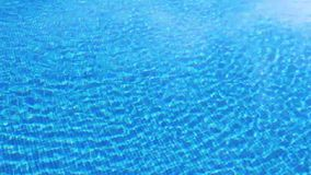 Wellenartig bewegendes klares Wasser im Swimmingpool mit blauer Unterseite, Draufsicht stock footage