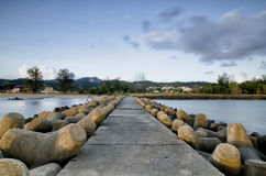Wellenbrecher entlang der Küstenlinie und der Betonmauer drastische und weiche Wolken mit blauem Himmel Lizenzfreie Stockfotografie