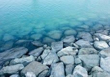 Wellenbrechersteine und -felsen nahe der Küstenlinie Stockfotografie