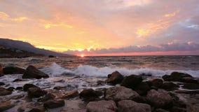 Wellenbruch über Steine bei Sonnenaufgang stock footage