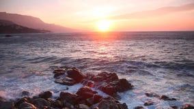 Wellenbruch über Steine bei Sonnenaufgang stock video