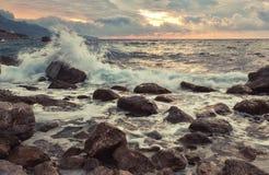 Wellenbruch mit spritzt über große Steine Stockfotografie