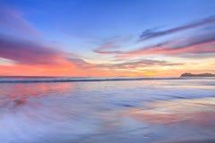 Wellenschaum, der den Strand weitergeht Stockfoto