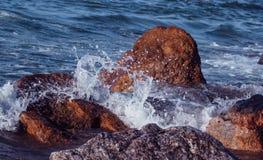 Wellenspritzen auf den Felsen stockbild