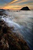 Wellenspritzen auf Riff bei Sonnenaufgang Stockbild