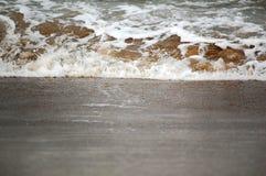 Wellenspritzen auf Sand Lizenzfreie Stockfotografie