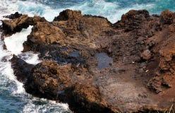Wellenspritzen gegen vulkanische Felsen Lizenzfreies Stockfoto