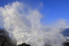 Wellenspritzen mit Regenbogen auf den Felsen Lizenzfreie Stockbilder
