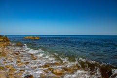 Wellenwicklungküstenlinie fallen an an Stockbild