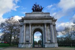 Wellington Arch or Constitution Arch is a triumphal arch located to the south of Hyde Park in London. Dramatic cloudy. Sky royalty free stock images
