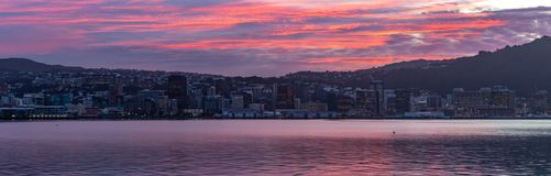Wellington, New Zealand, Panorama colorful sunset over calm harbor. Wellington, New Zealand, colorful sunset over calm harbor. Pink, Orange and red warm colours stock images