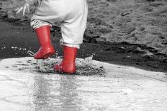 Wellingtons στη λακκούβα λαστιχένιες μπότες παιδιών στο υπόβαθρο θάλασσας Στοκ Φωτογραφίες