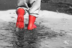Wellingtons στη λακκούβα λαστιχένιες μπότες παιδιών στο υπόβαθρο θάλασσας Στοκ Εικόνες