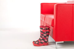 Wellingtons in front of a Red Couch. Pair of Stylish Wellingtons in front of a Red Couch on a White Isolated Background Stock Images