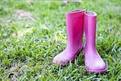 Wellingtons rosados en hierba Fotografía de archivo
