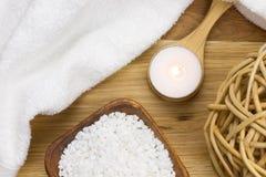 Wellness świeczka na drewnianej łyżce z ręcznikową i kąpielową solą zdjęcia stock