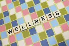 Wellness. The word 'wellness' spelled out in tiles on a pretty block background Royalty Free Stock Image