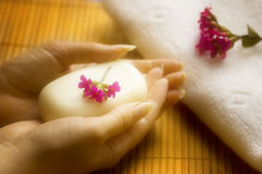 Wellness. Female hands keeping soap with flower on bamboo background stock images