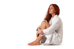 Wellness. Beautiful woman dressed in white bathrobe relaxes sitting on the floor stock photo