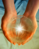 Wellness. Female hand keeping a saucer with water and a flare of light inside it royalty free stock photography