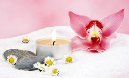Wellness. Two towels with a pink orchid and two candels Royalty Free Stock Photo