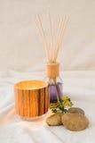 Wellness, aromatisk olja med en dekorativ tealight och stenar Fotografering för Bildbyråer