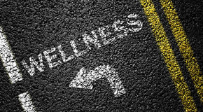 Wellness. And arrow on the asphalt road royalty free stock image