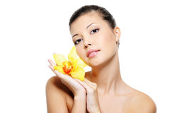 Wellness asian woman holding yellow flower. Face of a beauty wellness asian woman holding yellow flower on hands Royalty Free Stock Photos