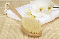 Wellness - bath brush on a folded towel with orchid Stock Image