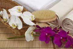 Wellness - Bath brush, rolled towels and orchids. A bath brush with purple and white orchids into a basket standing in front of some rolled towels and a pile of Stock Photo
