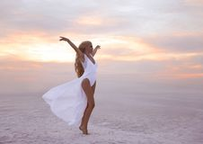 Wellness. Beautiful free confidence woman in white swimsuit enjoy summer vacation at sunset on the beach. Carefree blonde girl st. Anding with arms outstretched stock photo