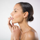 Wellness and beauty. A profile view of a pretty young woman lightly touching her lips with fingertips. Wellness and beauty concept Royalty Free Stock Photos