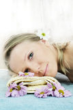 Wellness beauty portrait. Portrait of a fresh and beautiful blond woman on a towel with flowers Stock Photos