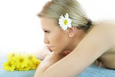 Wellness beauty portrait. Portrait of a fresh and beautiful blond woman on a towel with flowers Stock Image