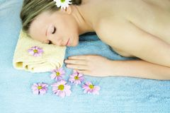 Wellness beauty portrait. Portrait of a fresh and beautiful blond woman on a towel with flowers Royalty Free Stock Images