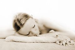Wellness beauty portrait. Portrait of a fresh and beautiful blond woman on a towel with flowers Stock Photography