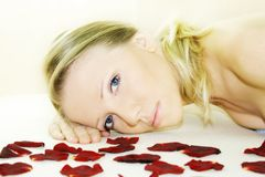 Wellness beauty portrait. A fresh and beautiful blond woman laying on a yellow towel with flowers Stock Images
