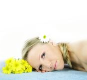 Wellness beauty portrait. Portrait of a fresh and beautiful blond woman on a towel with flowers Stock Photo