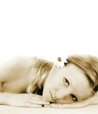 Wellness beauty portrait. Portrait of a fresh and beautiful blond woman on a towel with flowers Royalty Free Stock Photography