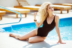 Wellness. Bikini model. Beautiful sexy woman with wavy hair in b. Lack bikini posing and sunbathing by the blue swimming pool on summer vacation Royalty Free Stock Photo