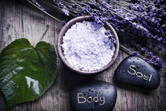 Wellness of body and soul. A green leaf with healing stones, a bowl with lavender herb salt and dry French lavender in old style like a concept for care and Stock Photos