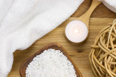 Wellness candle on a wooden spoon with towel and bath salt Stock Photos